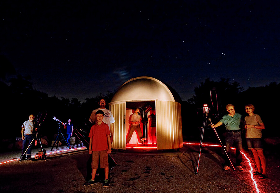 Children and adults enjoy astronomy at TPML with telescopes and an observatory under the night sky.