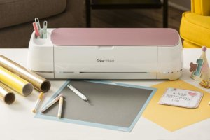 Cricut Maker with pink on top, pencils and paper scattered around it.